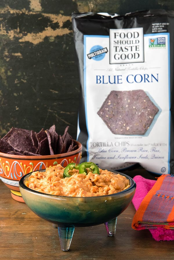 a bowl of spicy con Queso Dip next to a bag of Food Should Taste Good Blue Corn Chips