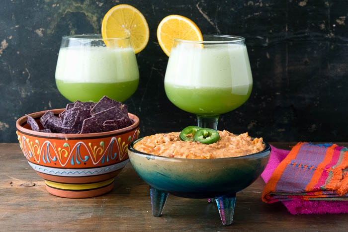 bowl of Chorizo con Queso Dip next to a bowl of Blue Corn Chips, with 2 Honeydew Margaritas behind the bowls