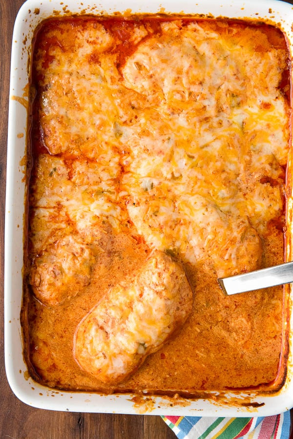 white casserole dish filled with gluten free enchiladas in sour cream sauce stuffed with chicken and green chiles