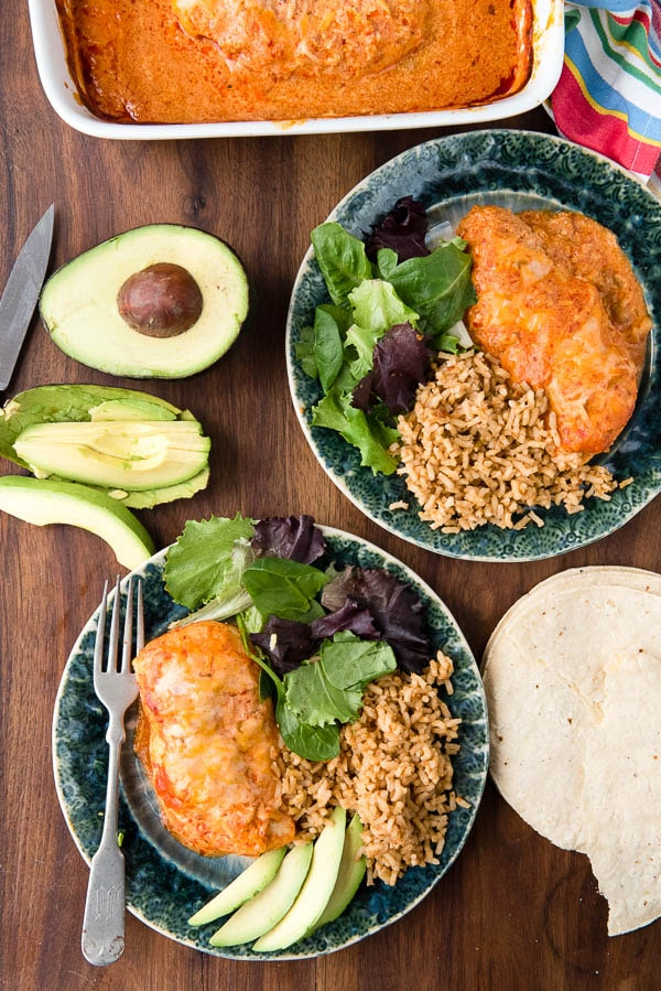 Mexican oven baked chicken breasts with rice and salad on green plates
