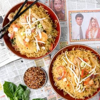 overhead image of 2 bowls of Singapore Street Noodles sitting on top of a Singapore newspaper. Black chopsticks perched on one bowl