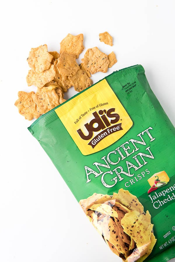 open bag of Udi's Jalapeno Cheddar Ancient Grains Crisps with a few chips outside of the bag