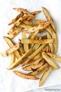 crispy homemade oven fries scattered on white parchment paper