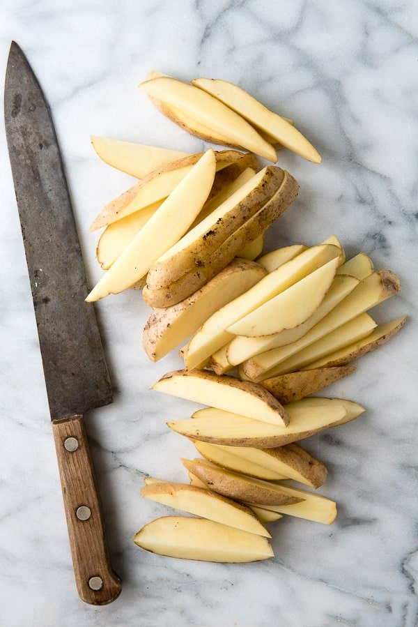 sliced potato wedges and a sharp chef's knife