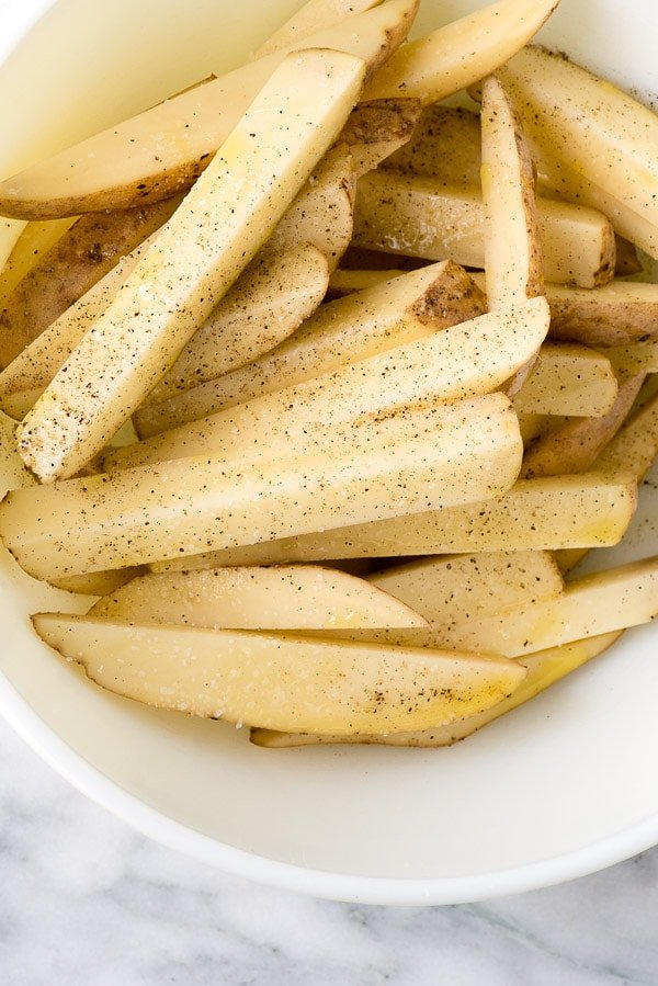 a bowl of Homemade Oven Fries seasoned with salt and black pepper