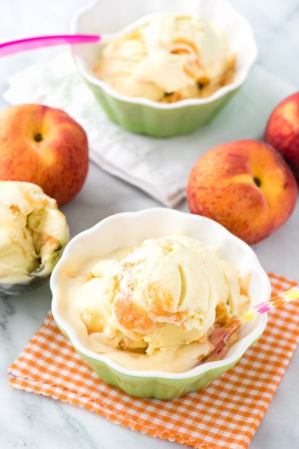 2 bowls of olive oil ice cream surrounded by fresh peaches