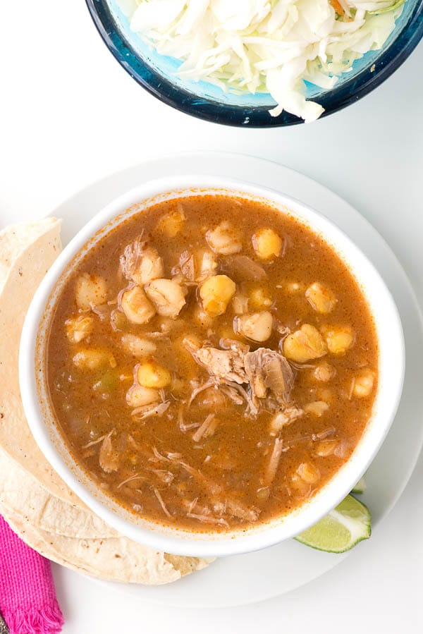 Posole with shredded pork in a white bowl