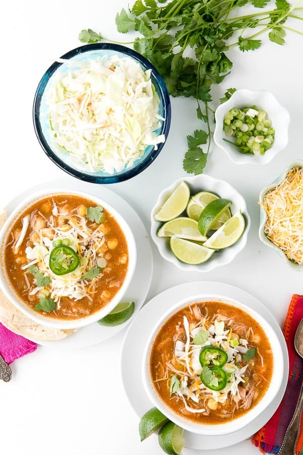 2 bowls of Posole Soup made in a slow cooker, surrounded by an assortment of garnishes for the hominy soup