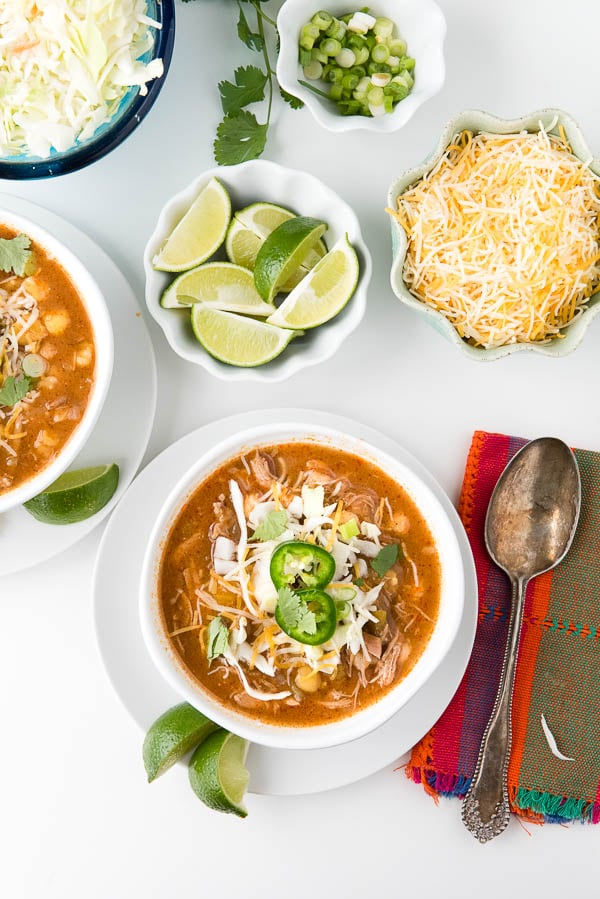 Red Posole in white bowls with garnishes