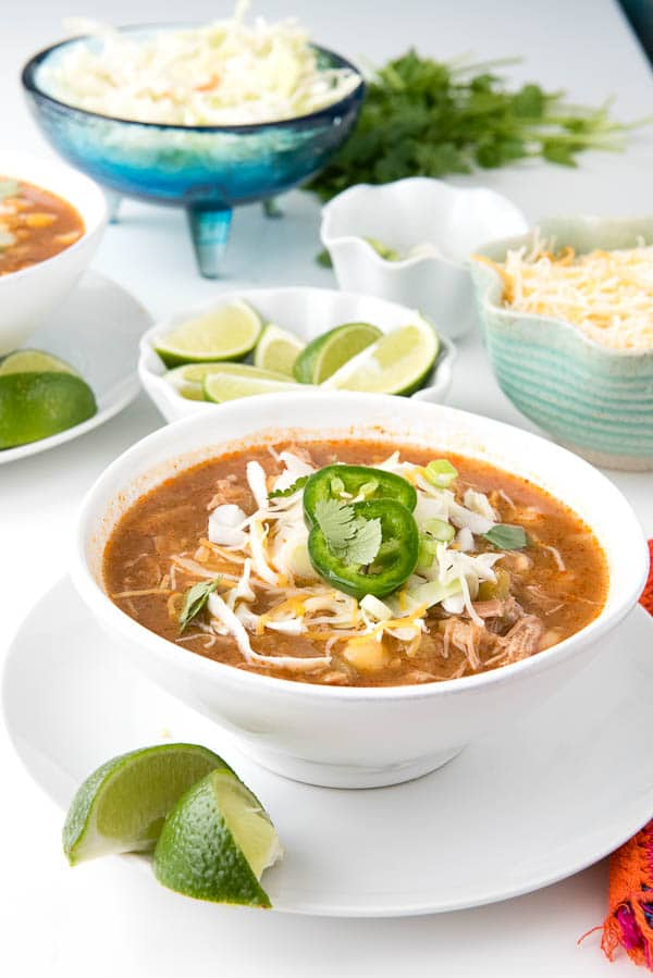 white soup bowl filled with red posole soup made in a slow cooker sitting on a white plate with lime wedges