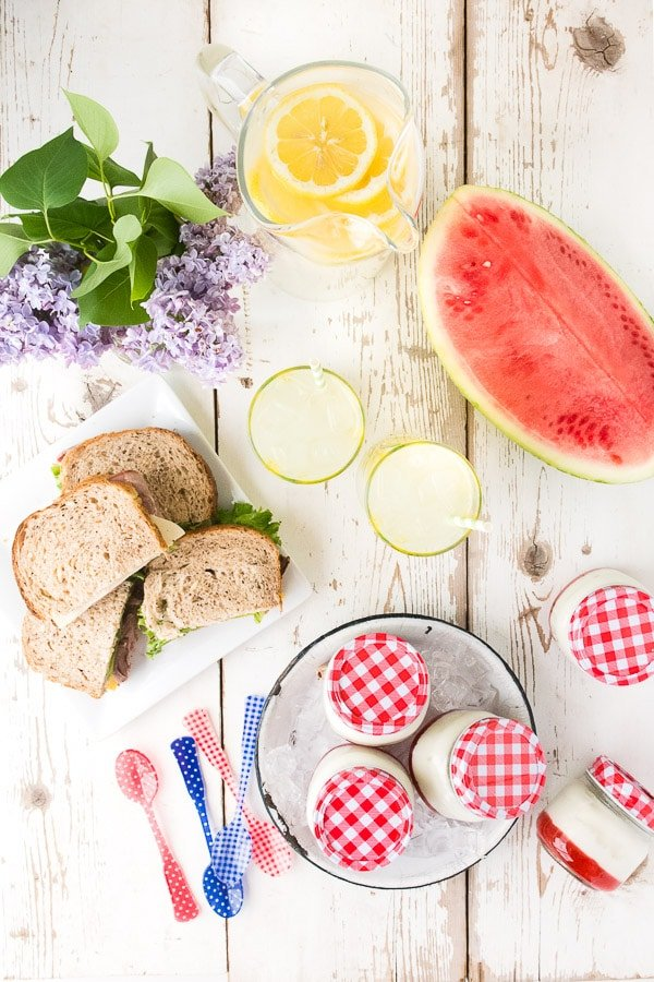 overhead image of a white wooden picnic table arranged with sandwiches, watermelon, lemonade, and portable panna cotta desserts made with strawberry jam