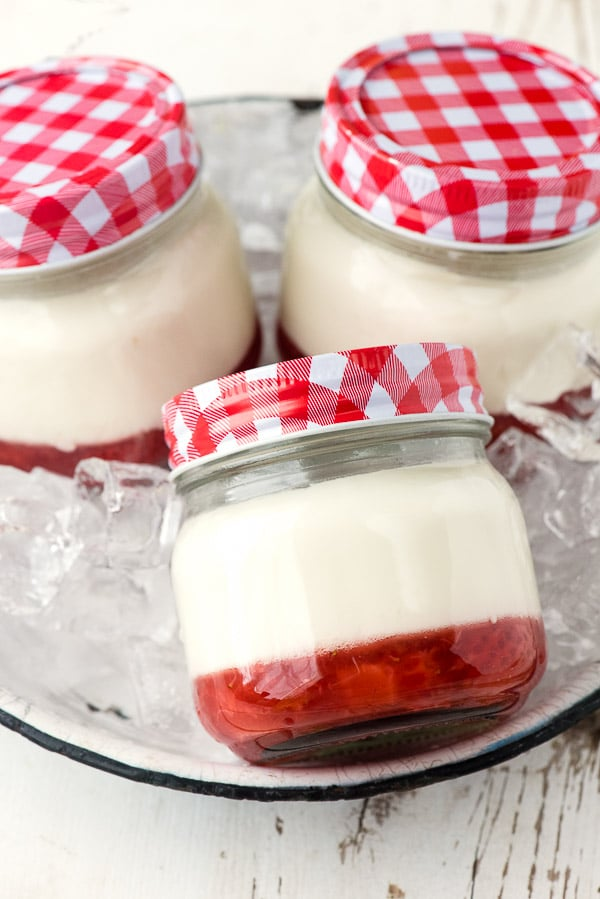 3 servings of Strawberry Jam Panna Cotta prepared in canning jars sitting in a serving tray filled with ice