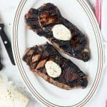 herb compound butter on grilled NY strip steaks