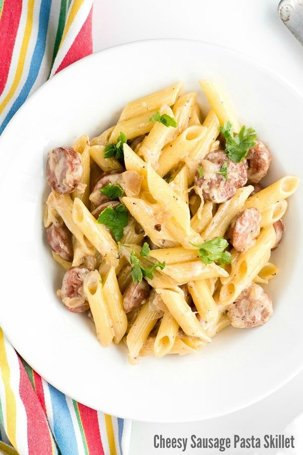 Bowl of Cheesy Sausage Pasta with shallot cream sauce and striped napkin