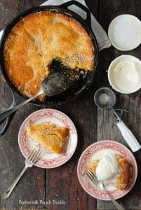 overhead view of  Buttermilk Peach Buckle in skillet and slices on plates