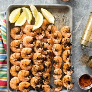 Grilled Spicy Salt and Pepper Shrimp Skewers on a baking sheet with lemon wedges