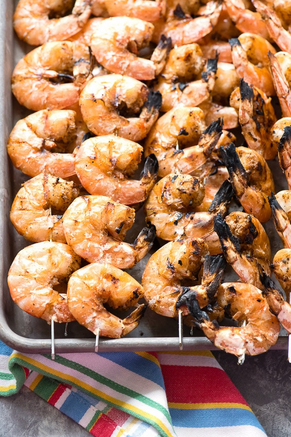 Grilled Spicy Salt and Pepper Shrimp Skewers on a baking sheet with striped towel