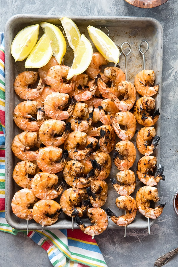 Grilled Spicy Salt and Pepper Shrimp Skewers with lemon wedges on baking sheet