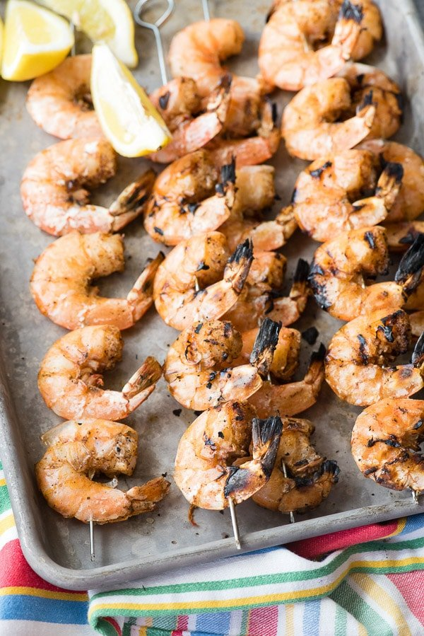 Grilled Spicy Salt and Pepper Shrimp Skewers with lemon wedges on a baking sheet