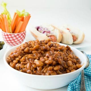 Slow Cooker Barbecue Beans with Bacon with hot dogs in background