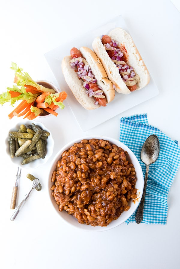 Slow Cooker Barbecue Beans with Bacon with hot dogs, sliced vegetables