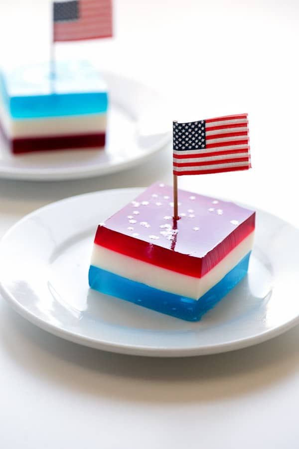 Layered red white and blue finger jello squares on a white plate