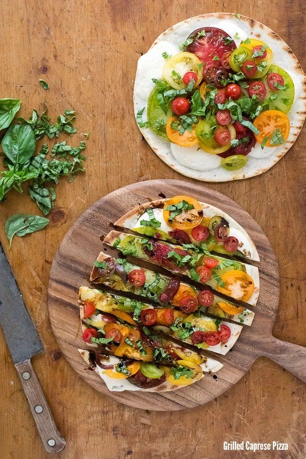 Grilled Caprese Pizza. A super simple recipe that uses a prepared pizza crust (gluten-free or regular) heaped with fresh tomatoes, buffalo mozzarella cheese and basil. Done in about 10 minutes. - BoulderLocavore.com