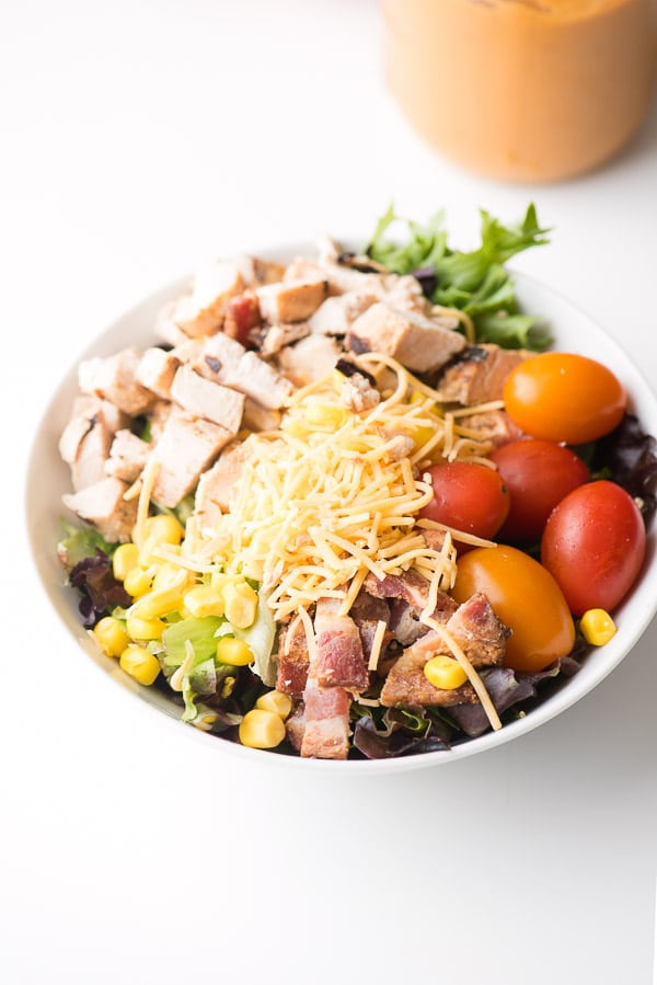 Mexican Cobb Salad with Roasted Tomato Dressing. A hearty, main dish salad bursting with flavor and color. Fresh lettuce, grilled chicken breast, bacon, cherry tomatoes, grated cheese, corn and Roasted Tomato Dressing - BoulderLocavore.com