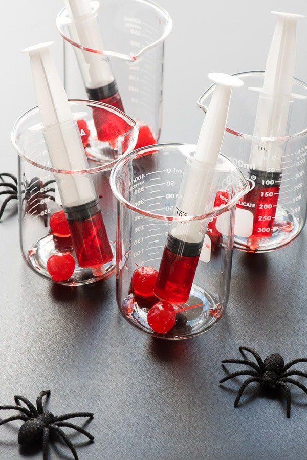 Beakers with large syringes of grenadine and maraschino cherries