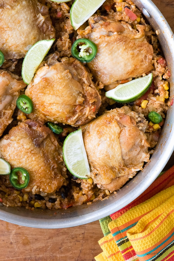 close up photo of Mexican Chicken and Rice Skillet in the skillet with lime wedges