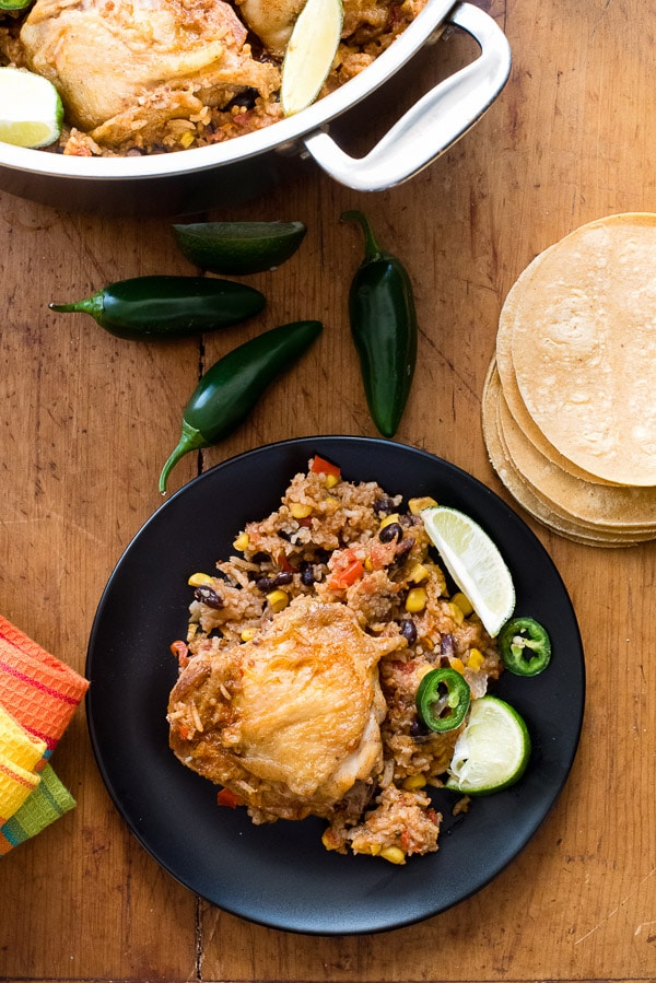 single serving of gluten-free Mexican Chicken and Rice Skillet on a black plate with fresh whole jalapeno peppers and part of the skillet