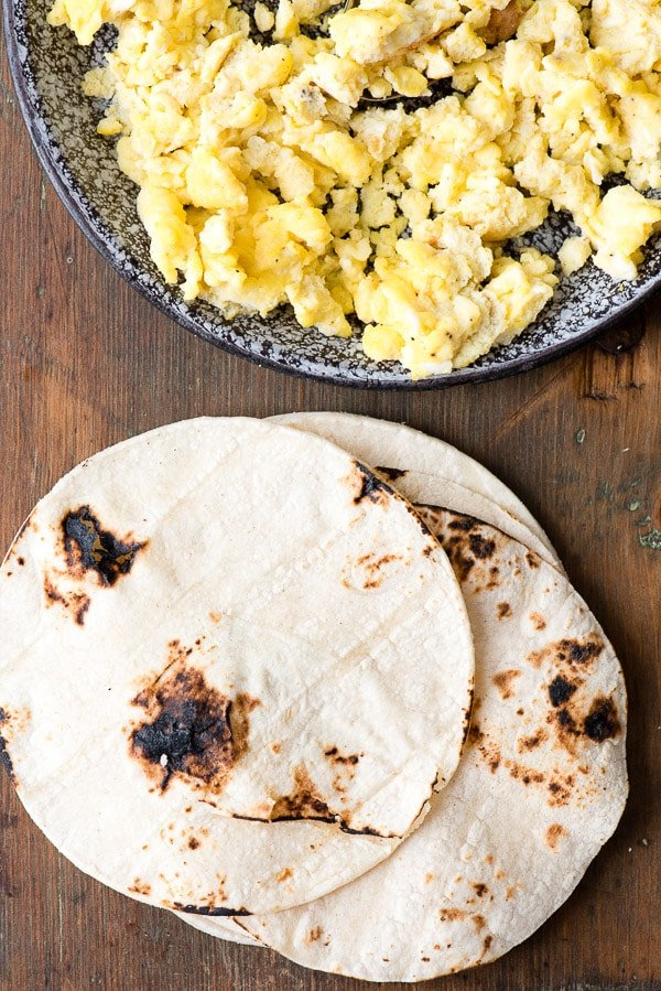 Scrambled Eggs and toasted Corn Tortillas for Sausage and Peppers Breakfast Tacos. A hearty start to the day with colorful bell peppers, onions, scrambled eggs, breakfast sausage and smoked cheese! | BoulderLocavore.com