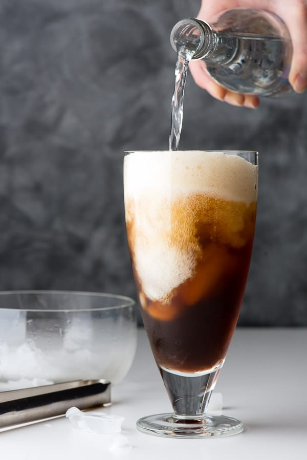 Pouring club soda into a glass of coffee and ice