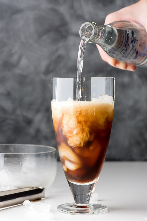 Pouring carbonated water into a glass of ice and coffee