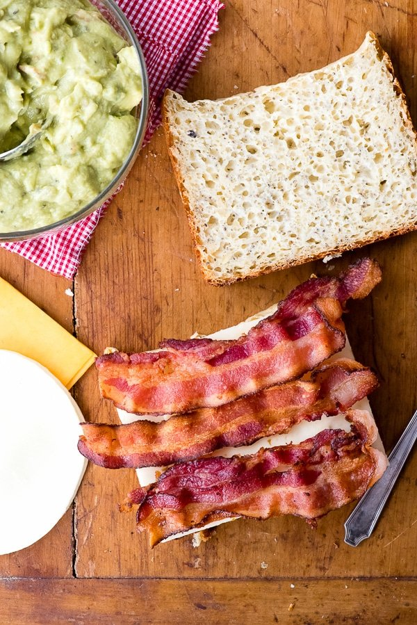 bacon on cheese sandwich with guacamole in bowl