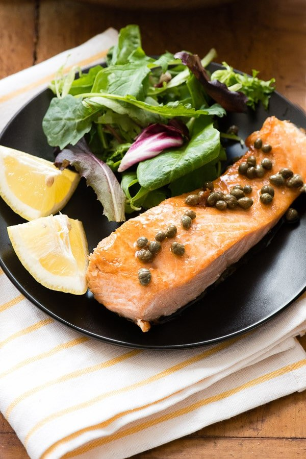 Pan Seared Salmon with Lemon and Capers on black plate with salad