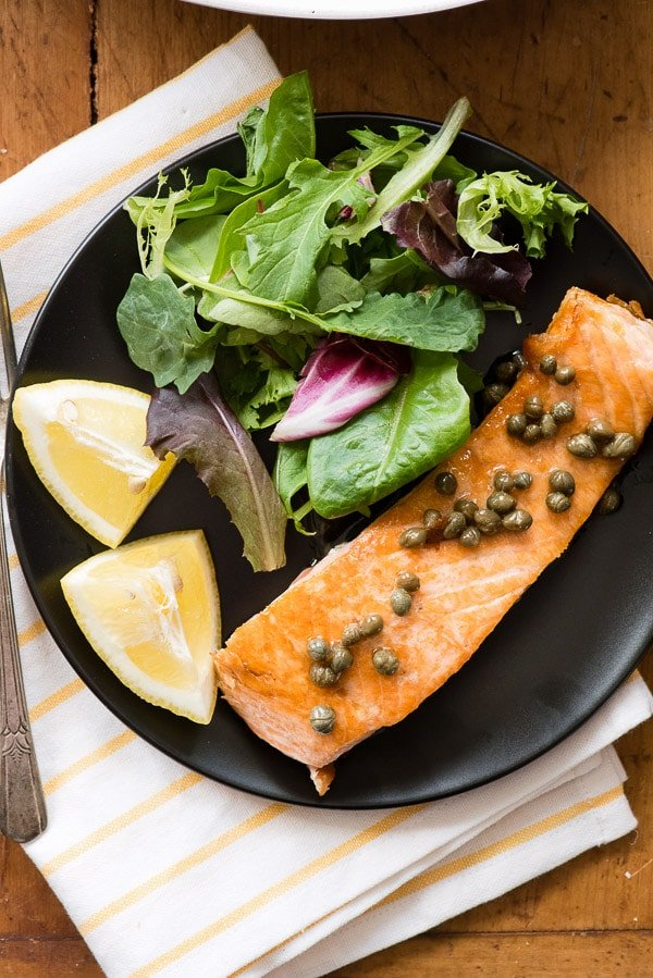 Pan Seared Salmon with capers and salad on a black plate