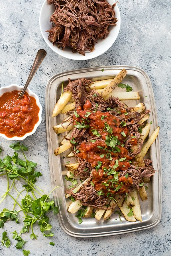 Slow Cooker Carne Asada with Oven Baked Fries. Easy slow cooked flank steak shredded over homemade fries makes a casual and filling dinner any day! BoulderLocavore.com