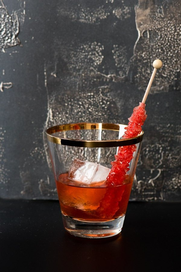 A glass cup on a table, with Old fashioned and Rye whiskey