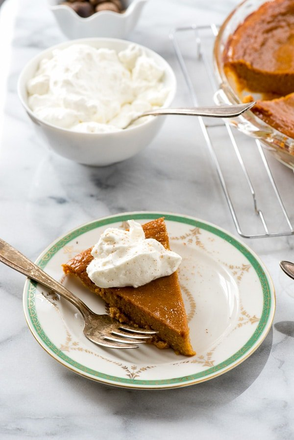 Slice of pumpkin pie without a crust on a plate with whipped cream on top