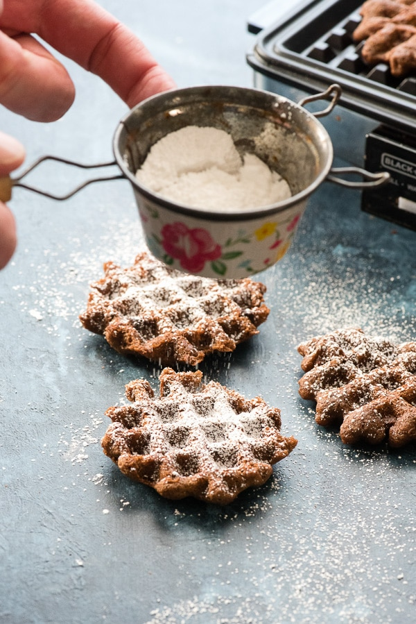 Sprinkling powdered sugar on Double Chocolate Mint Waffle Cookies