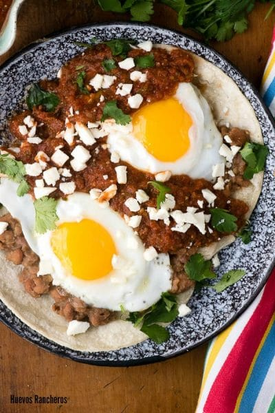 authentic Mexican recipe of Huevos Rancheros on a black speckled plate