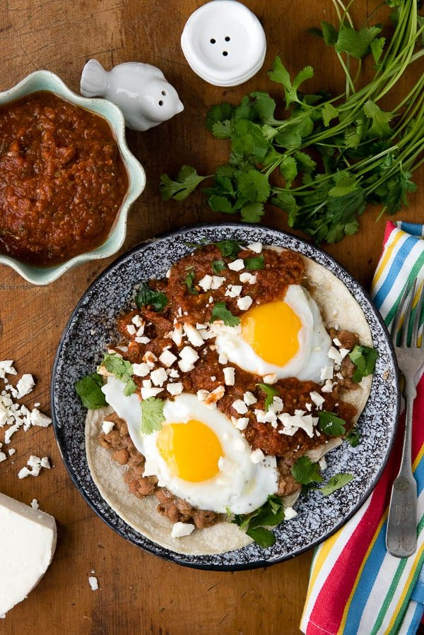 overhead image of a plate of Huevos Rancheros topped with fried eggs and a side of Rancheros sauce.