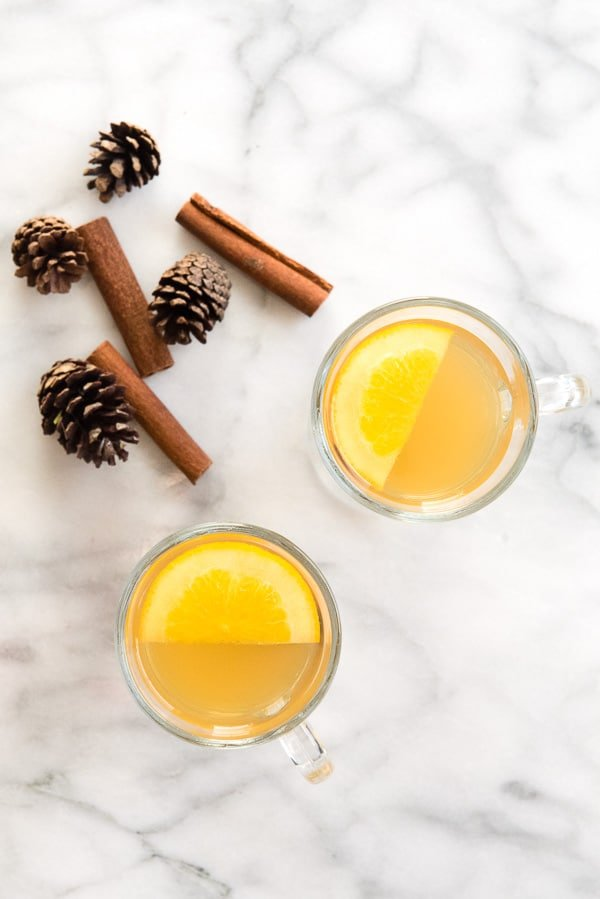 Top view of glass mugs of mulled apple cider with orange slices and cinnamon sticks