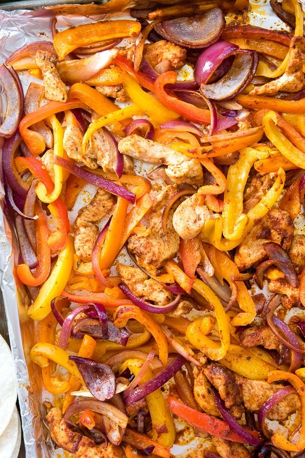 Sheet Pan Chicken Fajitas. The easiest (gluten-free) dinner recipe ever. Spicy chicken, peppers and onions cook in 20 minutes! Steaming hot from the oven to your table.- BoulderLocavore.com