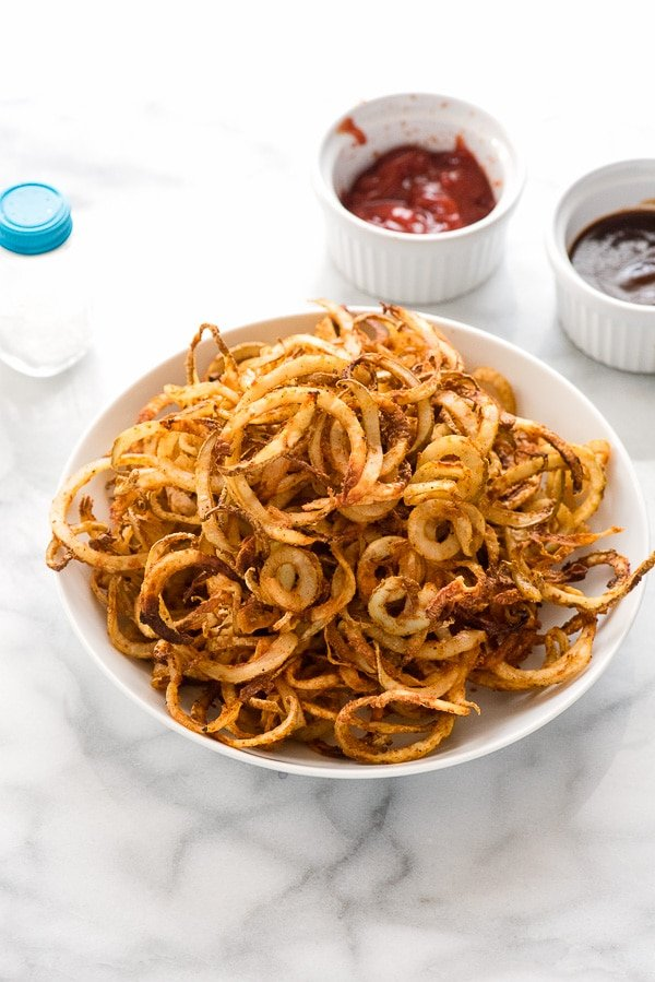 white bowl of spiralizer spicy baked curly fries with ketchup in ramekin