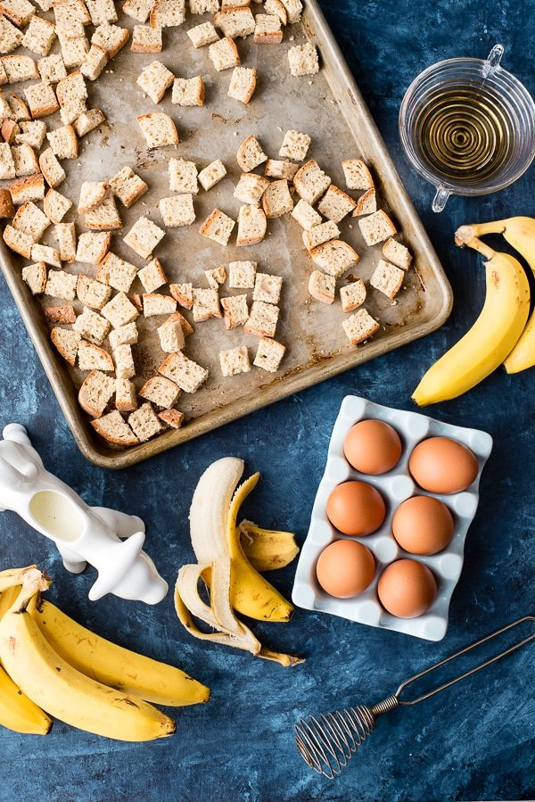 ingredients for bananas foster bread pudding (cubed bread on a rimmed baking sheet, peeled bananas, cream)