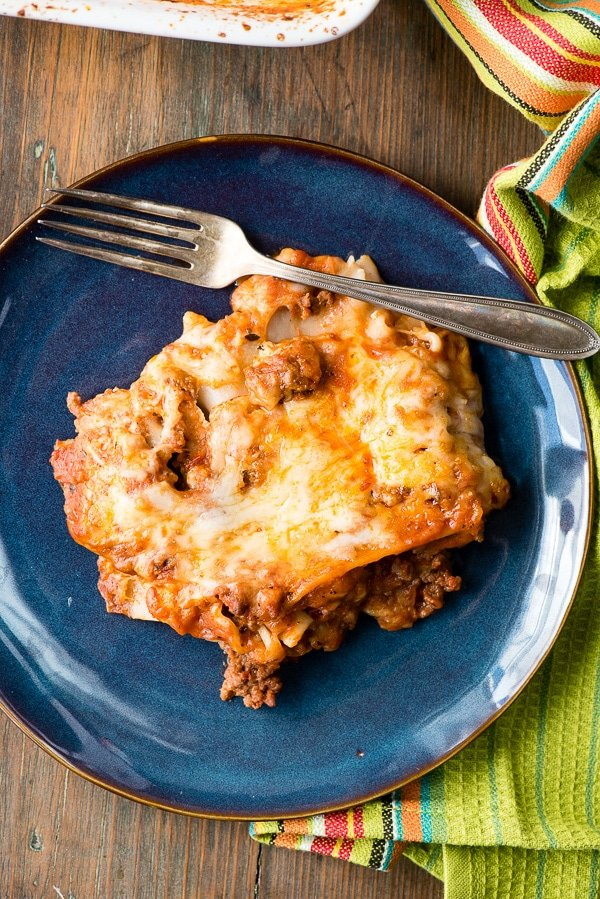 serving of meat and cheese lasagna with gluten-free noodles on blue plate from overhead