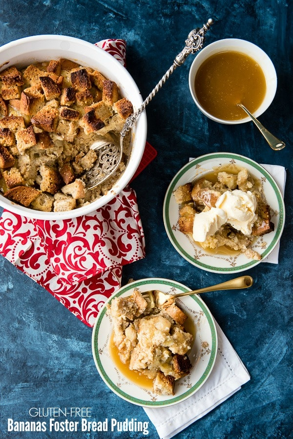 White baking dish of Bananas Foster bread pudding with servings in separate plates with recipe title on image