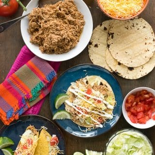 shredded taco chicken, tortillas and toppings for soft tacos